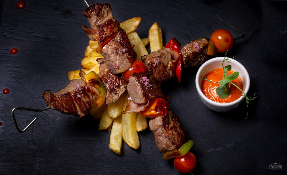 Sirloin, bacon and vegetables kebab with romescu sauce