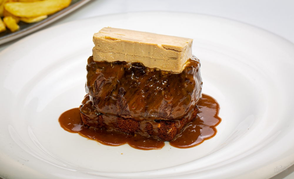 Sirloin steak with semi-cooked foie gras and Périgueux sauce (Tournedos Rossini) on its spice bread slice